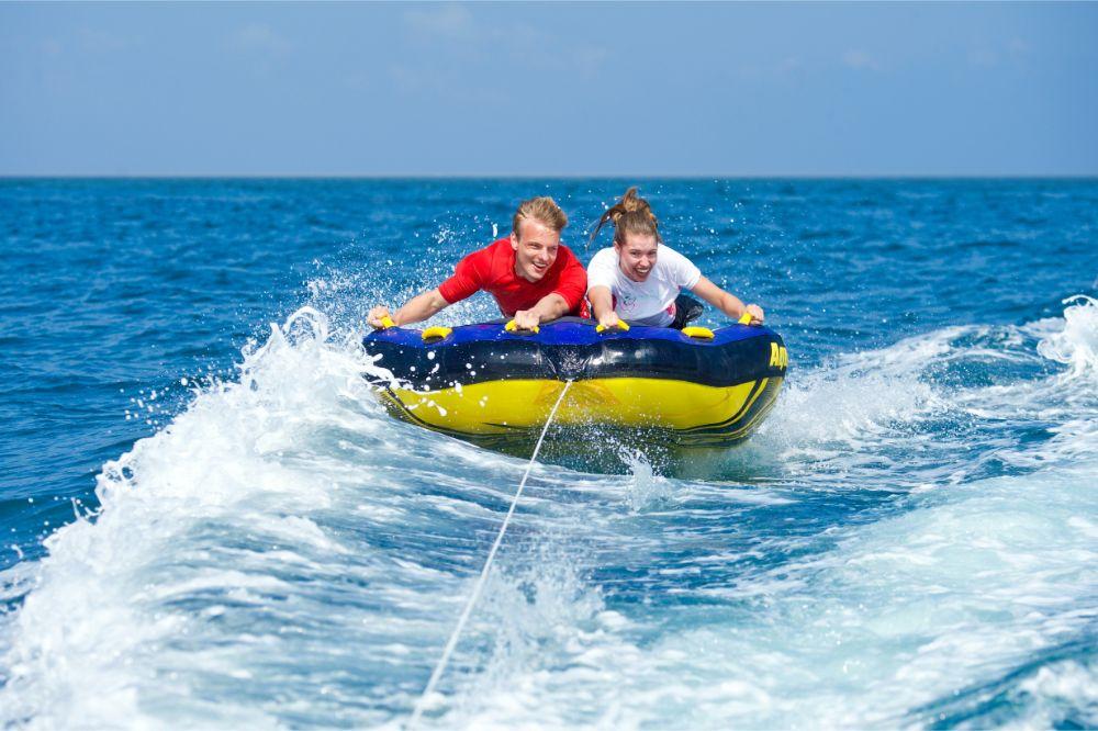 couple having fun riding the towable tube