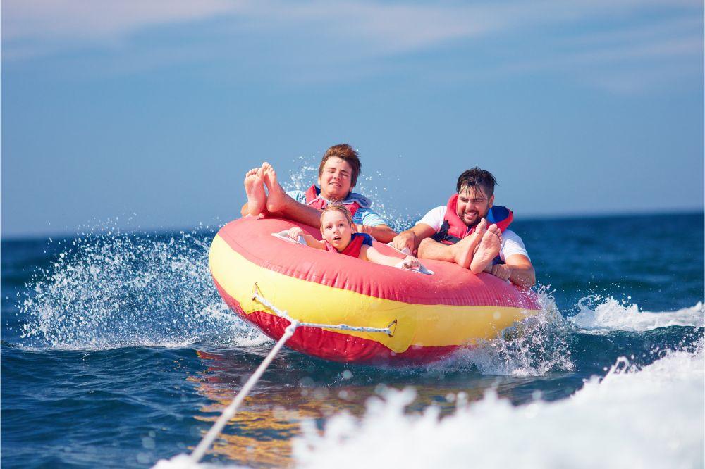 family having fun, riding on water tube